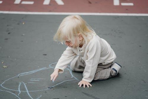 Cute girl sitting on asphalt with chalk