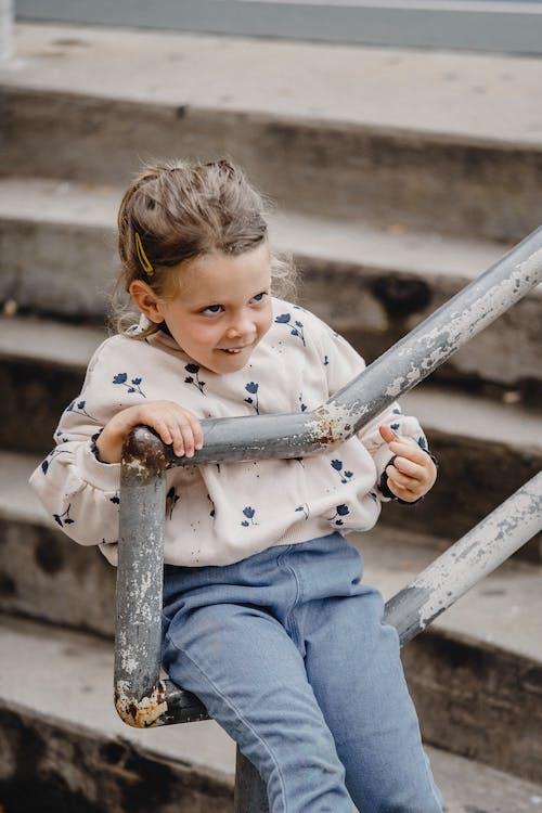 Little girl sitting on railing