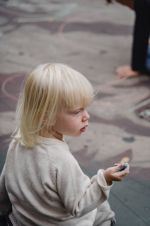 From above back view of cute little girl in casual wear sitting on asphalt ground with color chalk and looking away