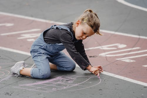 Focused girl drawing with chalks