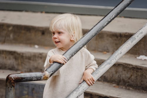 Side view of cheerful adorable little girl in casual outfit standing on staircase near railing and looking away