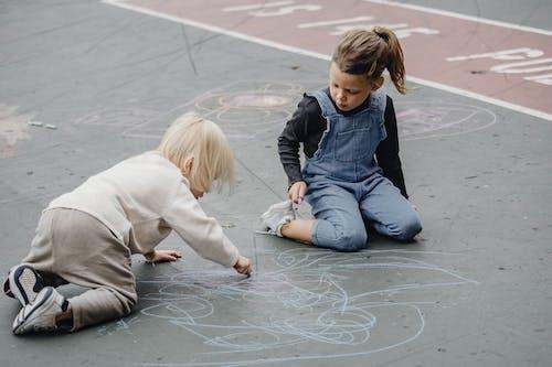 Adorable girls drawing on asphalt