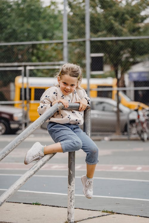 Full body delighted little girl in casual outfit sitting on metal railing and smiling while looking at camera