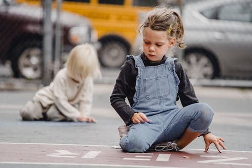 Full body little positive girl wearing casual jumpsuit drawing with chalks on asphalt road on street