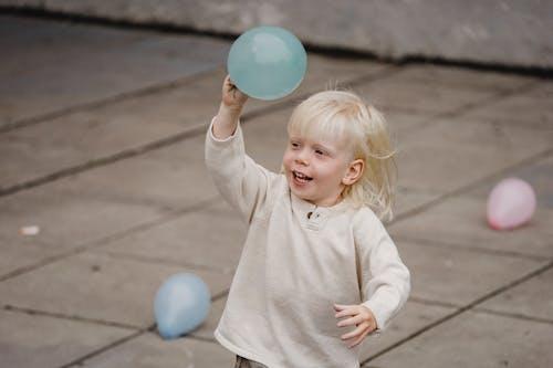 Happy little boy raising hand with balloon on street
