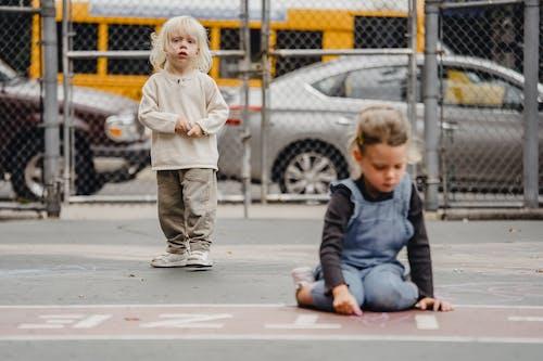 Kids with chalks spending time on sidewalk