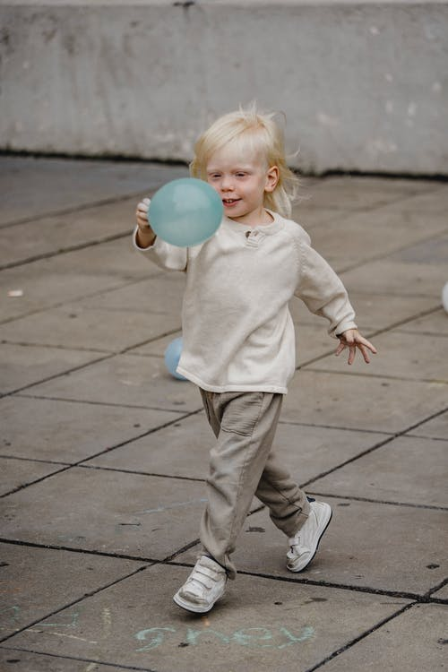 Adorable boy with balloon walking on pavement