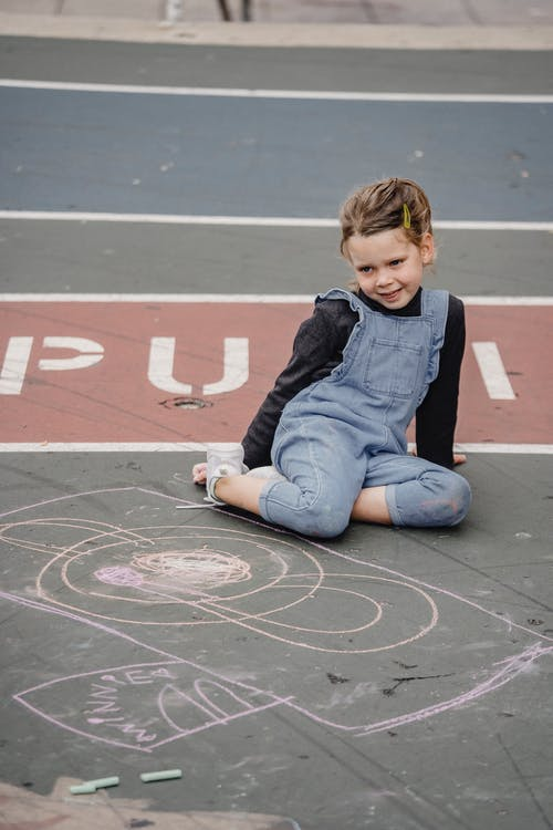 Full length content girl in casual clothes sitting on asphalt ground near chalk drawing and looking at camera with pretty smile