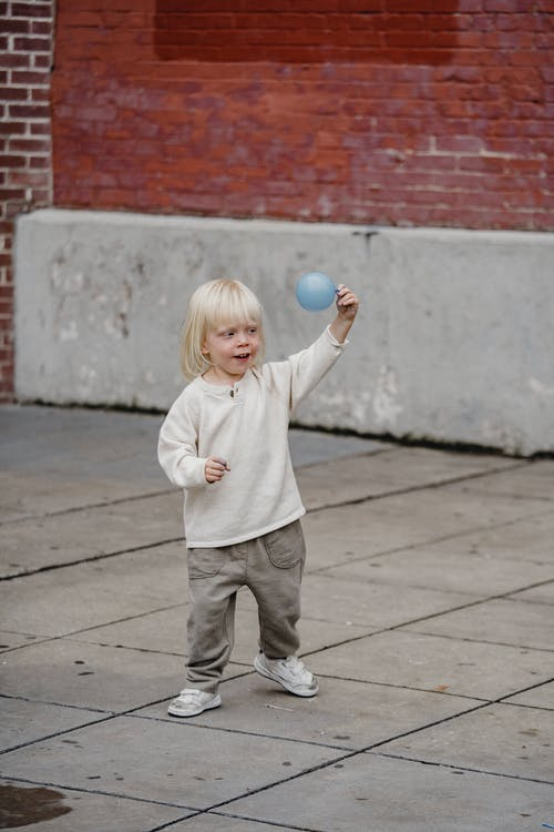 Cheerful boy with balloon playing on pavement