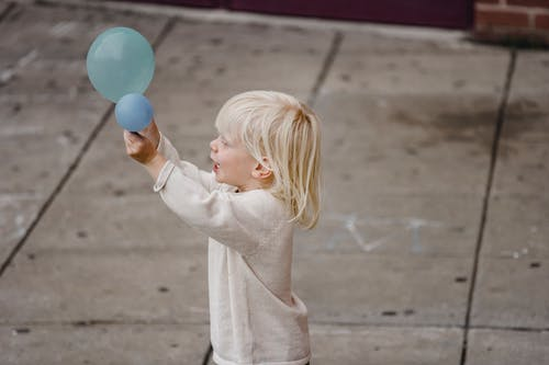 Happy boy playing with balloon on street