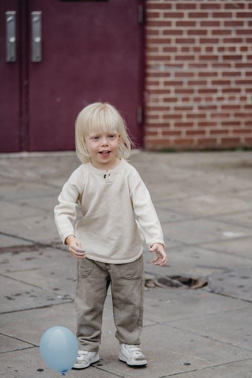Cute boy standing near balloon outside brick building
