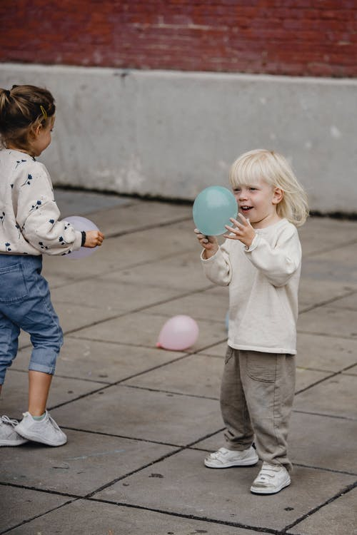 Cheerful girls playing with balloons on pavement
