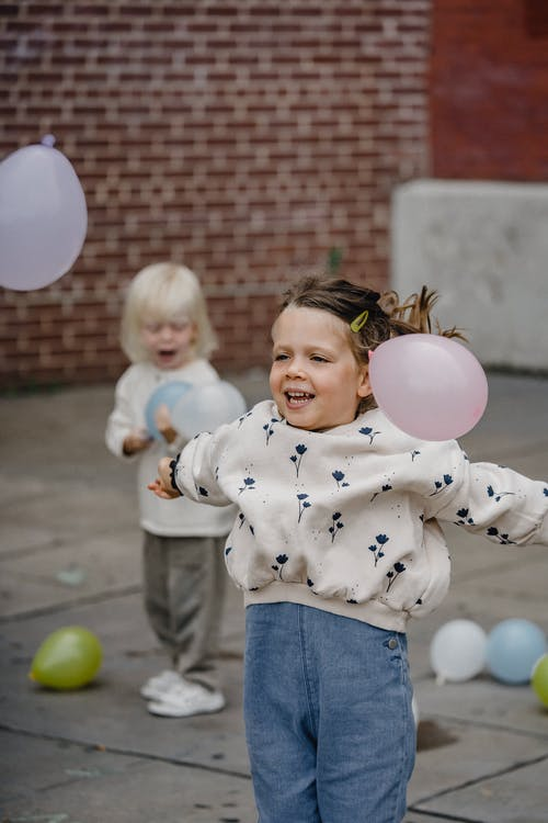 Happy children having fun with balloons on street