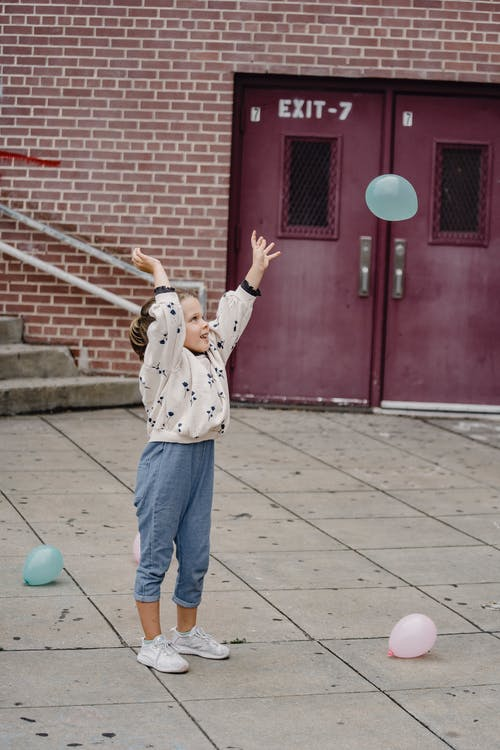 Cheerful girl playing with balloons on pavement in town