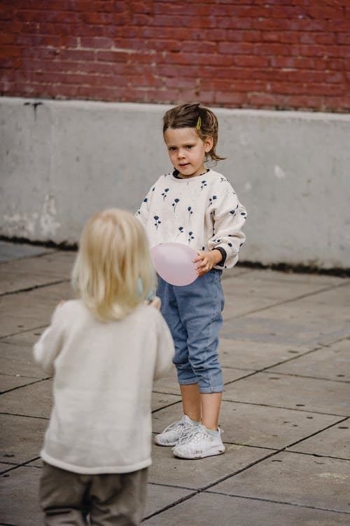 Unrecognizable kid interacting with girlfriend on urban pavement