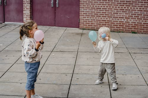 Girlfriends playing with balloons on urban pavement