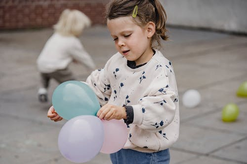 Crop charming child in ornamental apparel standing with assorted balloons on street with anonymous best friend playing in daytime