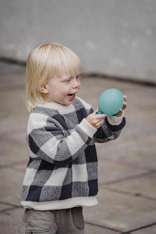 Cute little girl playing with balloon on street