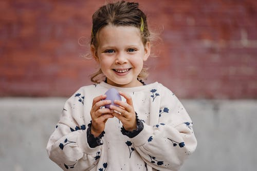 Candid child in casual clothes looking at camera with small balloon in town in daylight
