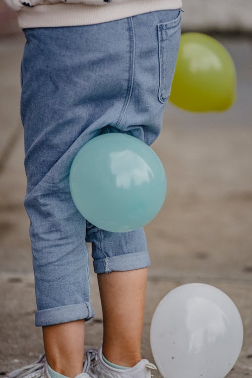 Faceless child playing with balloons on street