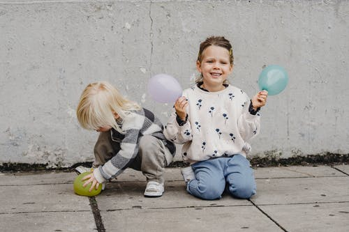 Smiling girl with balloons near unrecognizable best friend on street