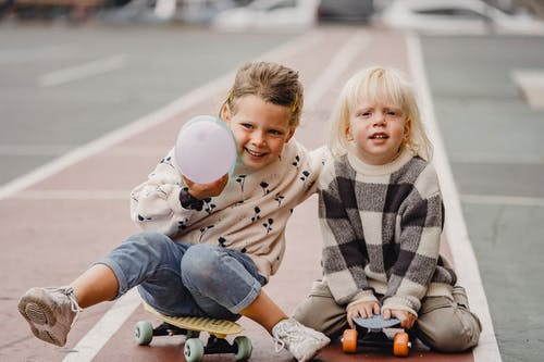 Happy kids sitting on longboards outside