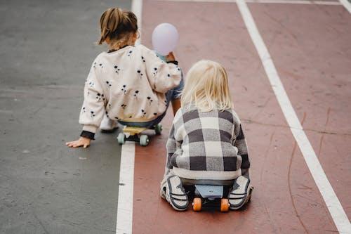 Faceless children sitting on skateboards on asphalt road