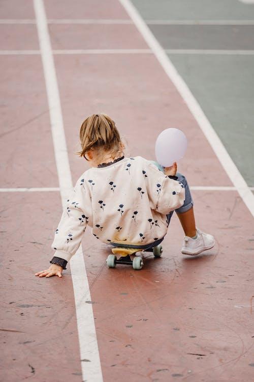 Faceless kid sitting on skateboard outside