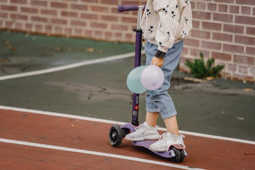 Anonymous child sitting on skateboard outside