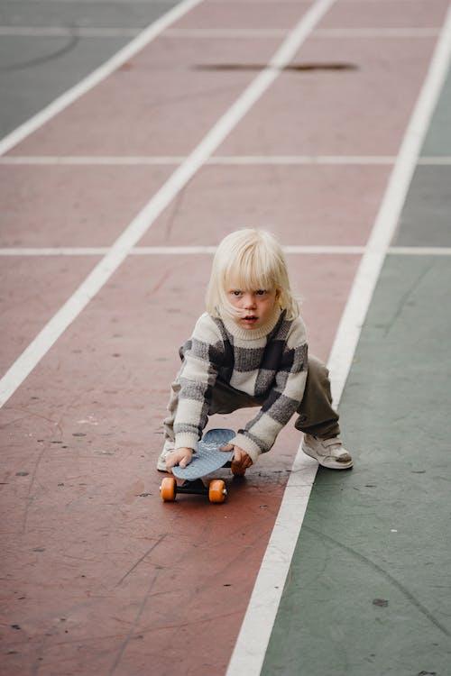 Kid holding skateboard on asphalt road