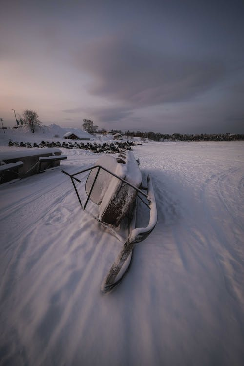 Forgotten snowmobile covered with hoarfrost and placed on side on snow in winter time  in field against cloudy sky