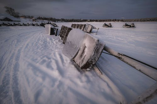 Snowmobile covered in ice placed on side on snow in field with forest in distance in winter time in nature outside