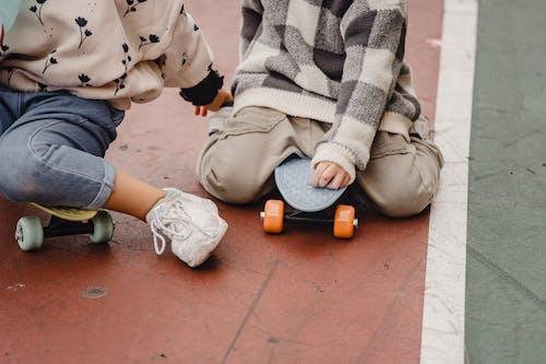 Faceless children sitting on skateboards on road
