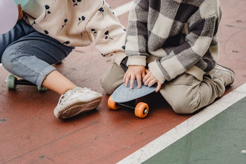 Anonymous kids sitting on longboards outdoors