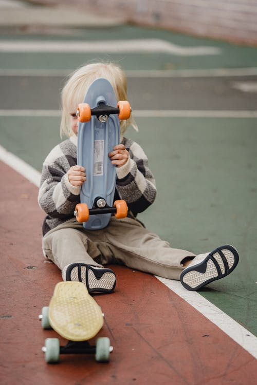 Anonymous little kid with penny board on playground