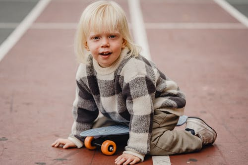 Full body of playful little kid looking at camera while sitting on sports ground with penny board against blurred background