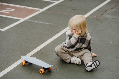 From above of full body of little kid with hand on face sitting on sports ground with penny board on street