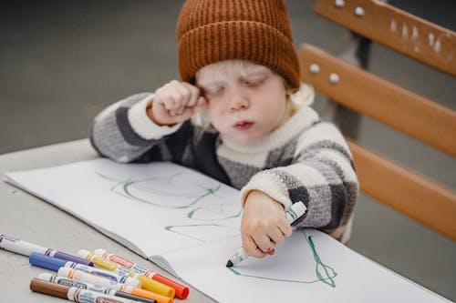 Kind In Witte En Bruine Trui En Oranje Gebreide Muts Met Pen