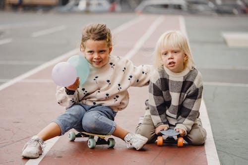 Children sitting on skateboards on street