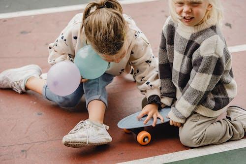 Kids sitting on longboards on asphalt road