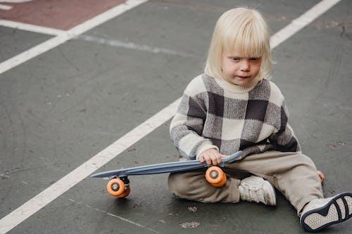 Meisje In Grijze Vacht Zittend Op Grijs Skateboard