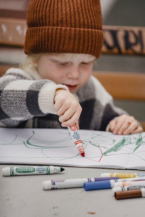 Kind In Witte En Zwarte Trui Met Witte En Rode Pen Schrijven Op Wit Papier