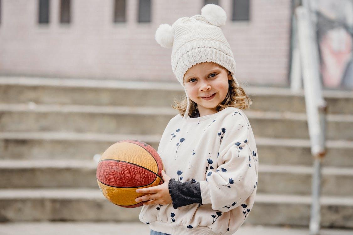 Meisje In Het Witte En Blauwe Bloemenbasketbal Van De Gewaadholding