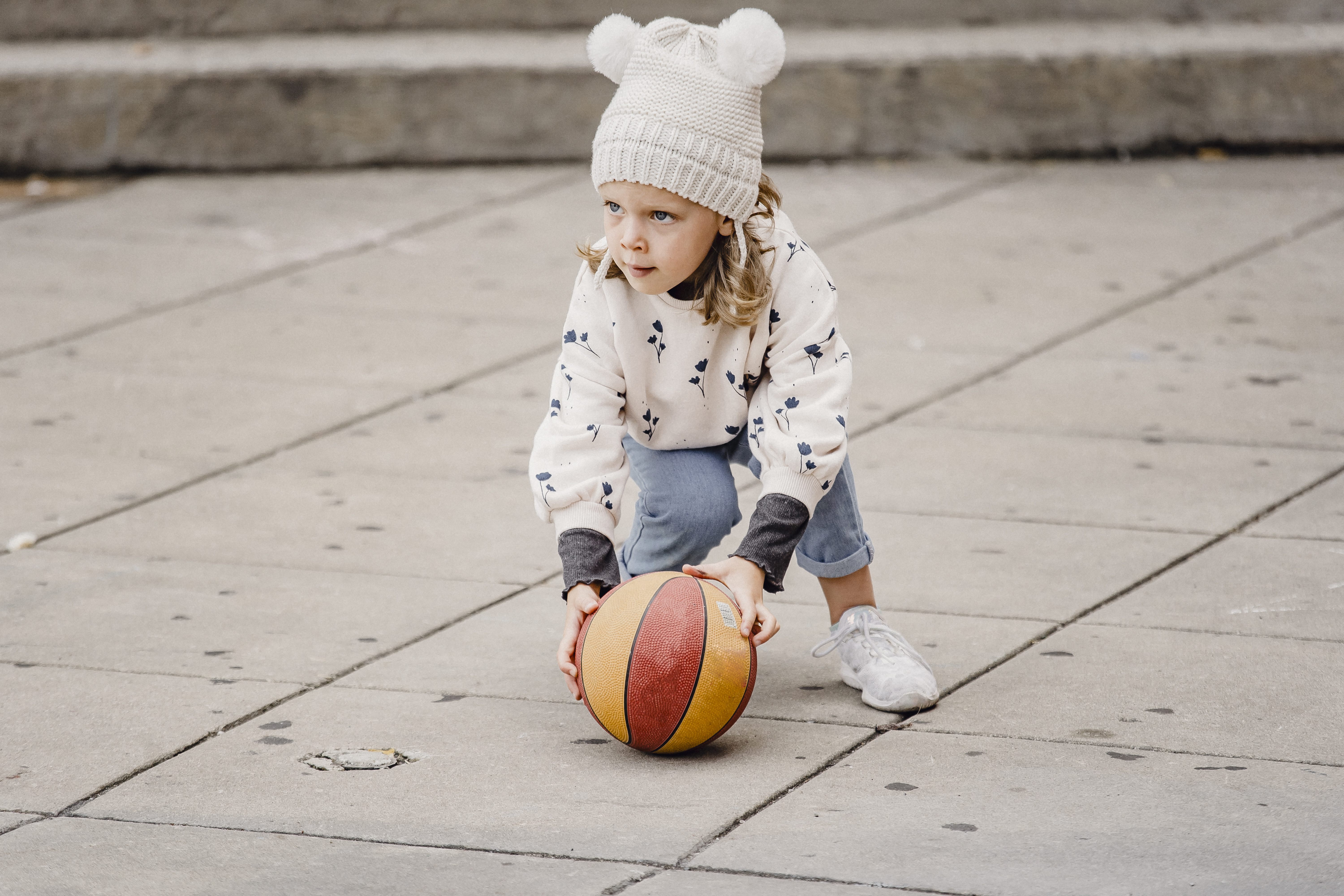 girl playing with ball on street