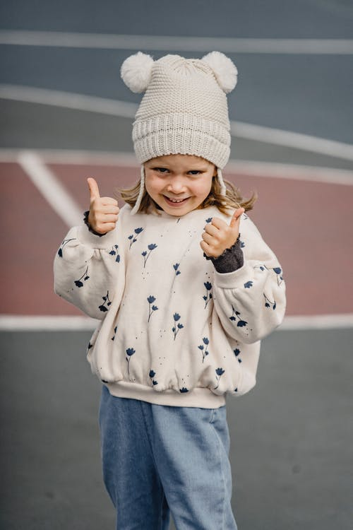 Little girl in jeans white jumper and hat showing thumbs up standing in playground and looking at camera