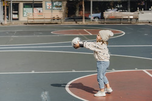 Cheerful girl playing ball on sport ground
