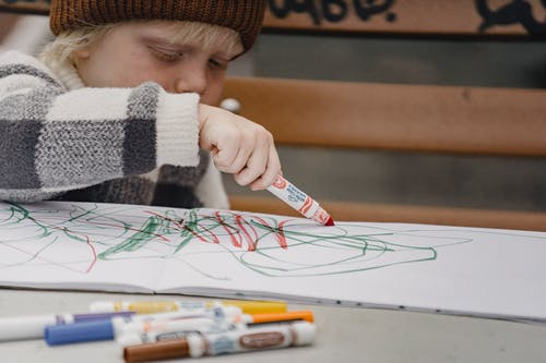 Little blond kid drawing in sketchpad using colorful markers sitting at table on playground
