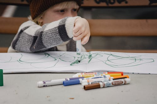 Child drawing with markers sitting at table on playground
