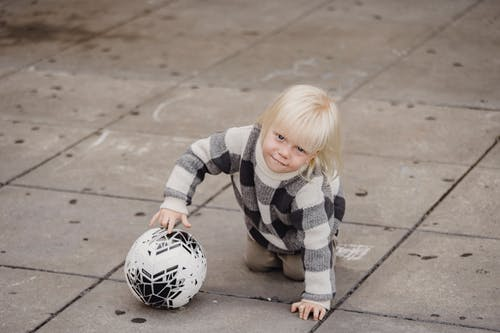 Little blond child in warm jumper playing with ball crawling on ground on play yard and looking at camera