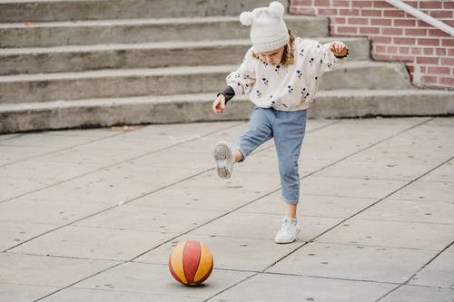 Niño En Chaqueta De Lunares Azul Y Blanco Y Pantalones Vaqueros Azules Jugando Baloncesto